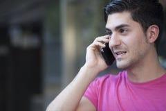 年轻人画象在都市背景中谈话在电话 免版税库存照片
