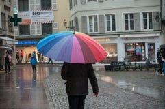 人画象有伞的在大卵石主要地方在城市 库存图片