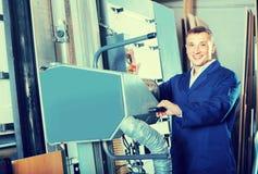 人画象运转在大自动锯machin的制服的 免版税图库摄影