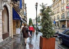 人们走在大道路易丝的雨期间在布鲁塞尔 免版税库存照片