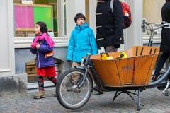 人们走通过有大木货舱的一辆自行车在Utr 免版税图库摄影