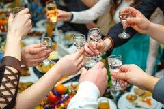 人们递使叮当响的玻璃用伏特加酒和酒 免版税库存照片