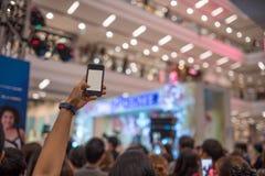 人们递使用拍在音乐会的智能手机照片 免版税库存图片
