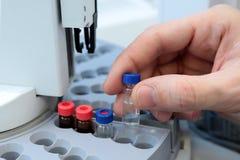 人们递拿着分析的试管小瓶集合在气体液体色谱分析仪 插入实验室的实验员 免版税库存图片