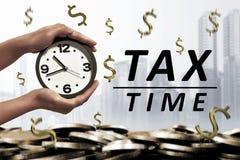 人们递拿着在税时间消息旁边的闹钟 免版税库存照片