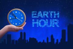 人们递拿着有地球小时问候的一个时钟 图库摄影