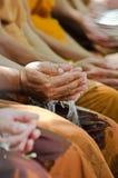 人们通过倾吐水庆祝Songkran入修士` s手 库存照片