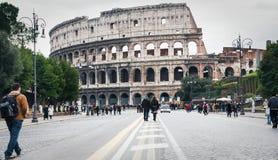 人们通过dei Fori Imperiali和colosseum 库存照片