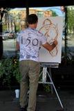 年轻人绘画马和车手在繁忙的街市街道上,萨拉托加,纽约, 2015年 免版税库存照片
