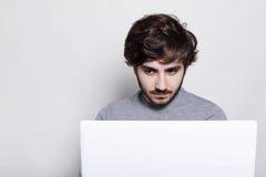 人们,情感,技术,教育 有时髦胡子的一个严肃的时髦的人与他的膝上型计算机一起使用 行家学生lookin 库存图片
