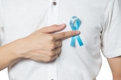 人` s医疗保健概念-接近指向前列腺癌的浅兰的丝带的男性手被隔绝的左胸口 免版税库存照片