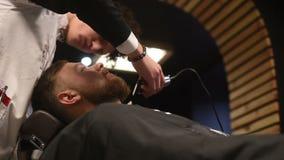 人` s发型和haircutting在理发店或发廊 修饰胡子 薄饼 人美发师做 股票录像