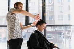 人` s发型和haircutting在理发店或发廊 库存照片