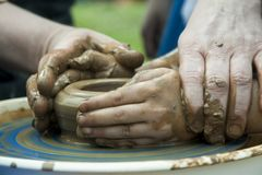 人` s和儿童在陶瓷工` s的` s手转动 库存照片