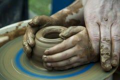 人` s和儿童在陶瓷工` s的` s手转动 图库摄影