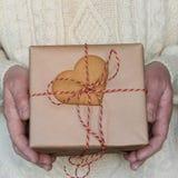 人` s手举行圣诞节或新年礼物盒用在毛线衣的曲奇饼 免版税图库摄影
