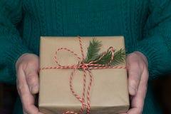 人` s手举行圣诞节有红色丝带的礼物盒在白色毛线衣 图库摄影