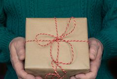 人` s手举行圣诞节有红色丝带的礼物盒在绿色毛线衣 库存照片