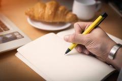 人` s手在有黄色笔的白色在木桌上的笔记本和新月形面包写了消息 免版税库存照片