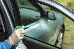 人` s手应用液体清洗车窗的挡风玻璃 免版税库存图片