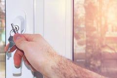 人` s手打开与钥匙的窗口 儿童` s安全 免版税库存图片