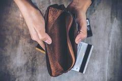 人` s手打开有信用卡的一个空的皮革钱包在桌上 图库摄影