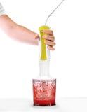 人` s手拿着有新鲜的一台搅拌器,并且明亮的草莓在搅拌器被混合,隔绝在白色背景 免版税图库摄影