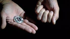 人` s手显示在黑背景的金黄和银色Bitcoin 股票视频