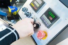 人` s手的特写镜头拿着在设备控制板的一台轮循交换机与仪器 免版税库存图片