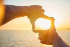 人` s手舒展往在海的太阳 一个人看日落通过被折叠的手指 库存照片