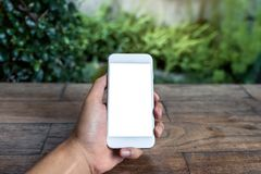 人` s手藏品和使用有黑屏的白色巧妙的电话的大模型图象在木桌和绿色自然上 库存图片