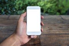 人` s手藏品和使用有黑屏的白色巧妙的电话的大模型图象在木桌和绿色自然上 图库摄影