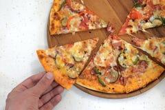 人` s手采取比萨饼从一块木板材的 在视图之上 白色桌背景 库存照片