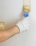 人` s手画油漆一条垂直线在墙壁上的 图库摄影
