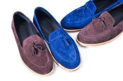 人` s皮革鹿皮鞋 时髦蓝色和米黄,在白色背景的两双对鞋子 库存图片