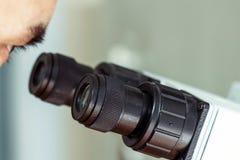 人` s眼睛通过显微镜看 专业实验室扩大化的设备特写镜头黑目镜  库存图片