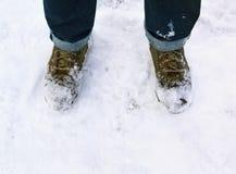 人` s脚和鞋子在雪 库存照片