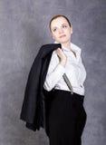 人` s衣服、白色衬衣和悬挂装置的美丽的女孩在灰色背景摆在 免版税图库摄影
