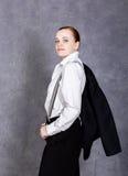 人` s衣服、白色衬衣和悬挂装置的美丽的女孩在灰色背景摆在 库存图片
