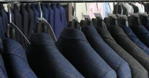 人` s衣服在裁缝` s商店 人` s手选择在他们的衣橱的一件夹克 男性选择 影视素材