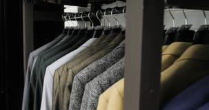 人` s衣服在裁缝` s商店 人` s手选择在他们的衣橱的一件夹克 男性选择 股票视频