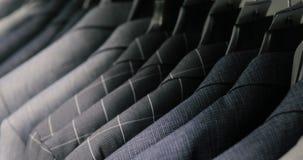 人` s衣服在裁缝` s商店 人` s手选择在他们的衣橱的一件夹克 男性选择 股票录像