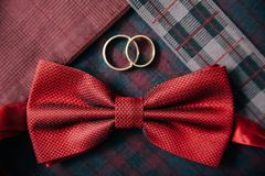 人` s辅助部件-蝶形领结,在纺织品背景的婚戒 免版税库存照片