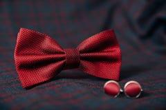 人` s辅助部件-蝶形领结,婚戒,在纺织品背景的链扣 免版税图库摄影