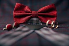 人` s辅助部件-蝶形领结,婚戒,在纺织品背景的链扣 免版税库存照片