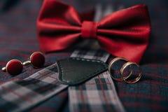 人` s辅助部件-蝶形领结,婚戒,在纺织品背景的链扣 图库摄影