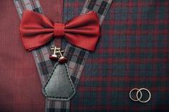 人` s辅助部件-蝶形领结,婚戒,在纺织品背景的链扣 免版税库存图片