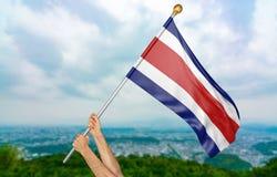 年轻人` s递骄傲挥动哥斯达黎加在天空的国旗,部分3D翻译 免版税库存照片