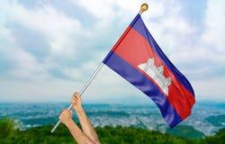 年轻人` s递骄傲挥动柬埔寨在天空的国旗,部分3D翻译 免版税库存照片
