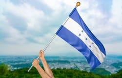 年轻人` s递骄傲挥动洪都拉斯在天空的国旗,部分3D翻译 库存图片